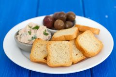 Pani tostati con il patè e le olive del pesce sul piatto Immagine Stock