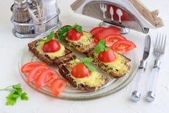 Pani tostati con la melanzana, il formaggio ed il pomodoro su una lastra di vetro immagini stock libere da diritti
