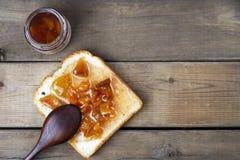 Pani tostati deliziosi con gli inceppamenti ed il cucchiaio dolci su fondo di legno, vista superiore, spazio della copia immagine stock