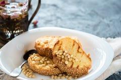Pani tostati di pane con il dolce casalingo dei semi di sesamo in pila decorata con il pinolo sul piatto bianco Fotografia Stock Libera da Diritti