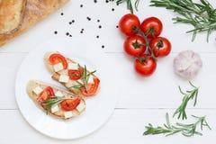 Pani tostati italiani di Bruschetta con i pomodori ed il formaggio su fondo di legno bianco, vista superiore fotografia stock