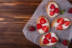 Pani tostati o Bruschetta con le fragole su formaggio cremoso su fondo di legno Fotografia Stock