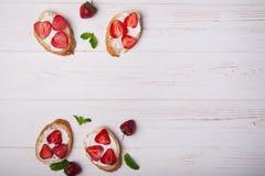 Pani tostati o Bruschetta con le fragole su formaggio cremoso su fondo di legno bianco Fotografia Stock Libera da Diritti