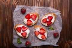 Pani tostati o Bruschetta con le fragole su formaggio cremoso su fondo di legno bianco Immagini Stock