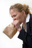 Panic attack. Blond woman holding a brown paper bag over mouth with a distraught expression as if having a panic attack or being nauseated Stock Image