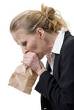 Panic attack. Blond Caucasian woman holding a brown paper bag over mouth with a distraught expression as if having a panic attack or being nauseated Stock Photography