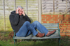 Panic attack man on a bench. A man sitting on a bench with his feet on the bench. His hands to his face, crying and  having a panic attack Royalty Free Stock Photography