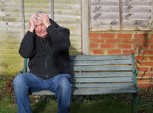 Panic attack man on a bench. A man sitting on a bench with his hands to his head having a panic attack Royalty Free Stock Image
