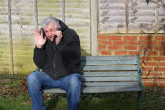 Panic attack man on a bench. A man sitting on a bench holding his hand out in front of him, crying having a panic attack Stock Photos