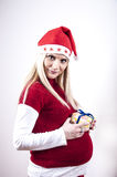 Panic pregnant woman with christmas hat and gift Royalty Free Stock Images