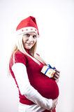 Panic pregnant woman with christmas hat and gift Royalty Free Stock Image