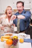 Panicked Couple in Kitchen Late for Work. Late for Work Stressed Couple Checking Time in Kitchen Royalty Free Stock Photos