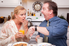 Panicked Couple in Kitchen Late for Work. Late for Work Stressed Couple Checking Time in Kitchen Stock Photos
