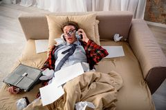 Panicked man looking at alarm in hand at home. Stop ringing. Scared guy lying in bed with frightened look. He is holding alarm clock while listening to it in Stock Photography