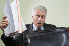 Panicked man looking in briefcase. Panicked men looking in briefcase Royalty Free Stock Images