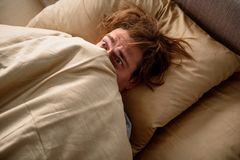 Panicked man unwilling to get up in the morning. Feeling frightened. Scared adult male lying in bed and covering his head with a blanket in bedroom Stock Image