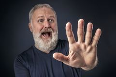 Panicked old man with his stretched hand forward. Old man in shirt and scared with his stretched hand forward Royalty Free Stock Photos