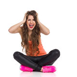 Panicked Woman Shouting. Young woman in orange shirt, black leather trousers and pink sneakers sitting on a floor with legs crossed, holding head in hands and Stock Photography