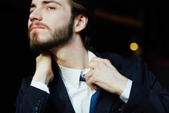 Panicking Businessman in Stress. Portrait of young bearded businessman tearing away the tie and shirt trying to get some air, having trouble breathing and Royalty Free Stock Photo