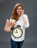 Panicking girl showing embarrassing alarm clock for tensed time management. Panicking beautiful girl showing an embarrassing alarm clock in her oversized hand Royalty Free Stock Photos