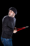 Panicky burglar. A burglar wearing black clothes holding huge wire cutters over black background royalty free stock photo