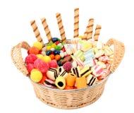 Panier avec de divers bonbons et les biscuits, d'isolement Photographie stock libre de droits