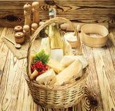 Panier avec de divers types de fromage et de vin sur le backgroun en bois photos stock