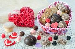 , Panier avec des bonbons et biscuits sur la table, coeur décoratif de Saint Valentin Images stock