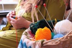 Panier avec des boules du tricotage de fil et de femme Photographie stock