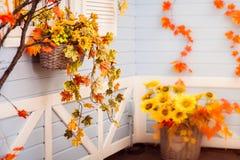 Panier avec des fleurs et des feuilles d'automne accrochant sur le mur bleu o Photos libres de droits