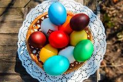Panier avec des oeufs de pâques sur une table en bois dehors Photos stock