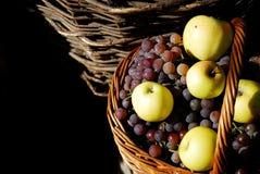 Panier avec des raisins et des pommes Photos stock