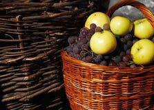 Panier avec des raisins et des pommes Images stock