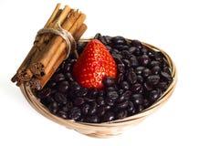 Panier avec du café, la cannelle et une fraise sur le CCB blanc Photo libre de droits