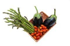 Panier avec le groupe d'asperge, de tomate et d'aubergines d'isolement Photos libres de droits