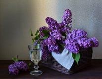 Panier avec le lilas et un verre de l'eau Image libre de droits