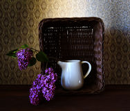 Panier avec le lilas et un verre de l'eau Photos stock