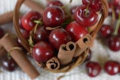 Panier avec les cerises rouges de tiges et le pot avec des cerises Photographie stock