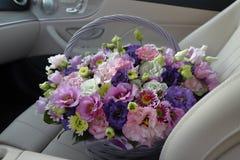 Panier avec les fleurs lilas sur le siège avant de la voiture photo stock