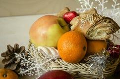 Panier avec les pâtisseries, la pomme, les mandarines, les cônes et les flocons de neige Photo libre de droits