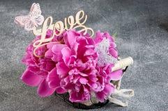 Panier avec les pivoines roses sur le fond gris Photo libre de droits