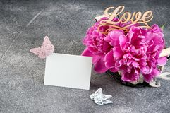 Panier avec les pivoines roses sur le fond gris Photos stock