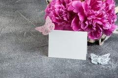 Panier avec les pivoines roses sur le fond gris Photo stock