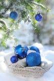 Panier blanc avec les boules décoratives de Noël sur la neige et les boules bleues sur l'arbre de Noël dehors Photographie stock libre de droits