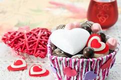 Panier coloré avec des bonbons et des biscuits sur la table, coeur décoratif de Saint Valentin Photos stock