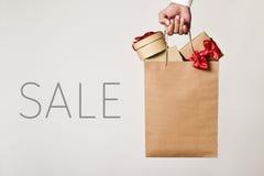 Panier con los regalos y venta de la palabra Fotografía de archivo