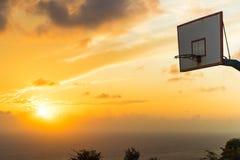 Panier de basket-ball contre le ciel de coucher du soleil Photo libre de droits