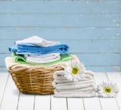 Panier de blanchisserie avec les serviettes colorées sur le fond images stock