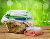 Panier de blanchisserie avec les serviettes colorées sur le fond photos stock
