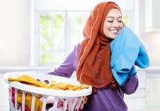 Panier de blanchisserie de transport de port de hijab de jeune femme tout en sentant photo stock